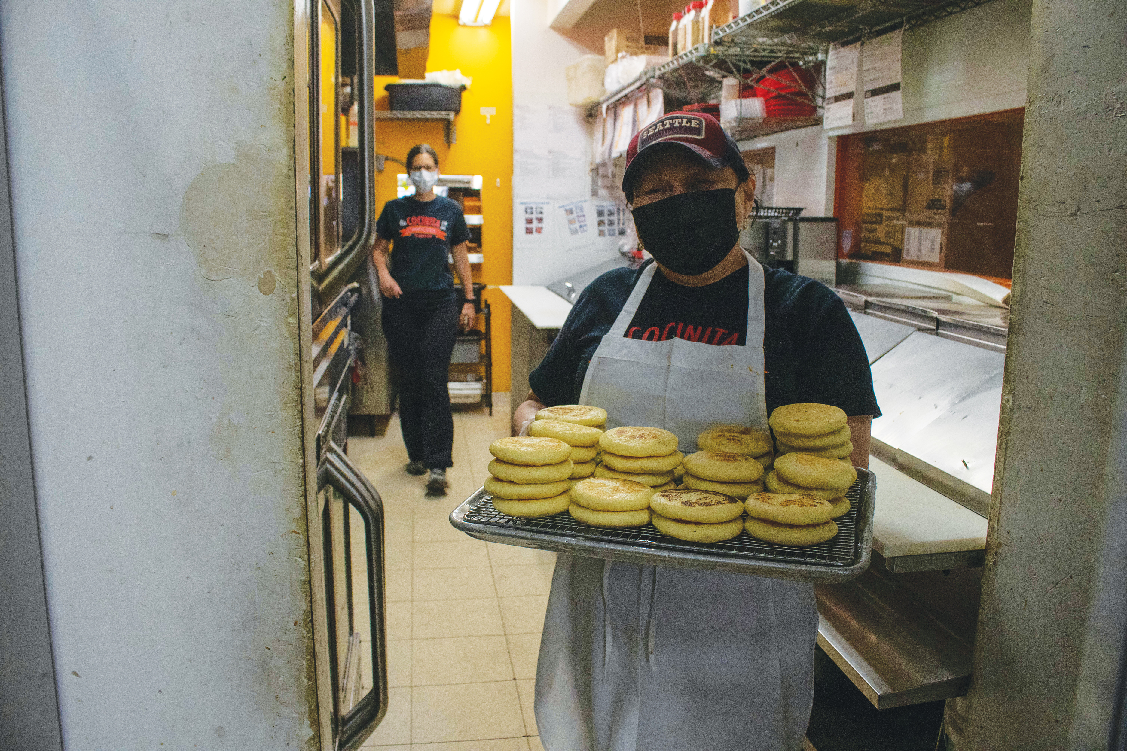 An employee holding a tray of arepas in the kitchen