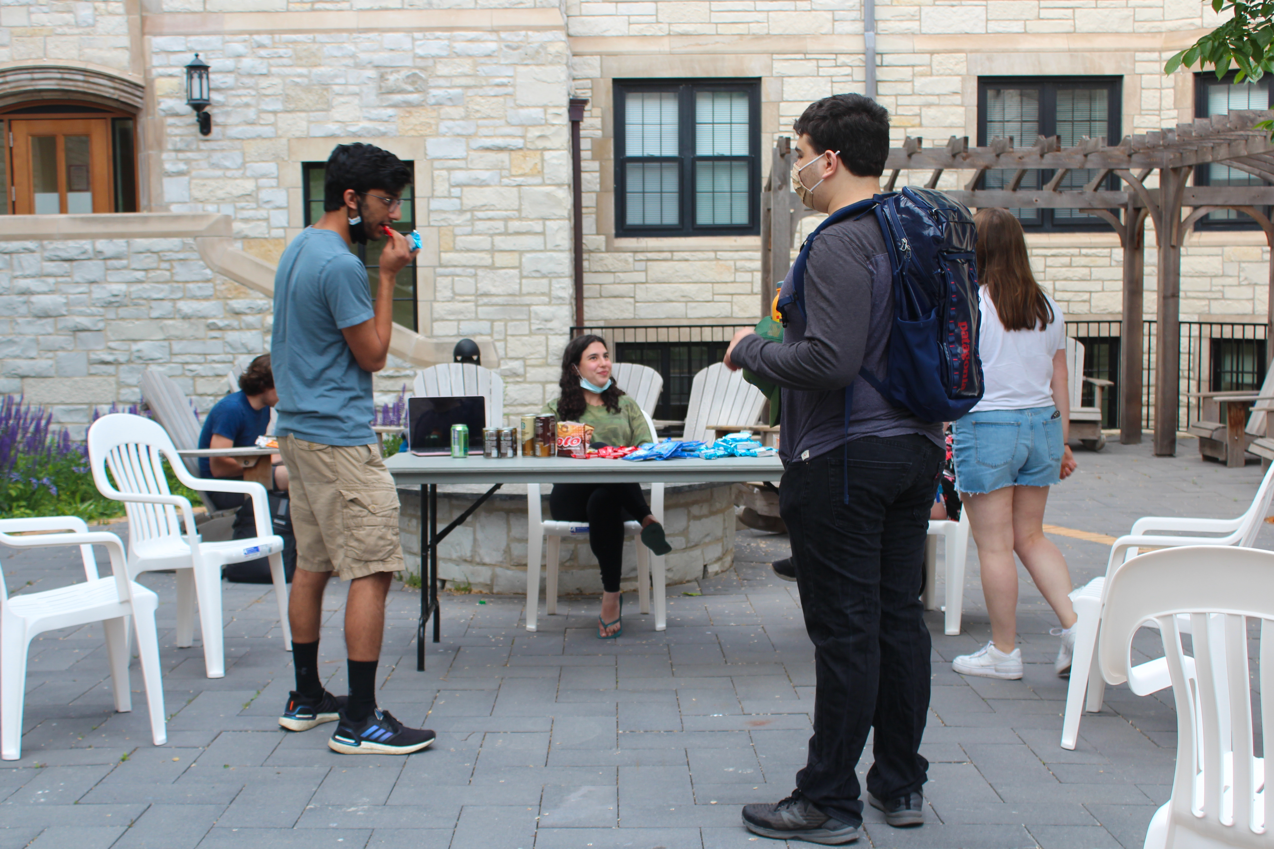 Photo of students standing around a table with snacks and coffee
