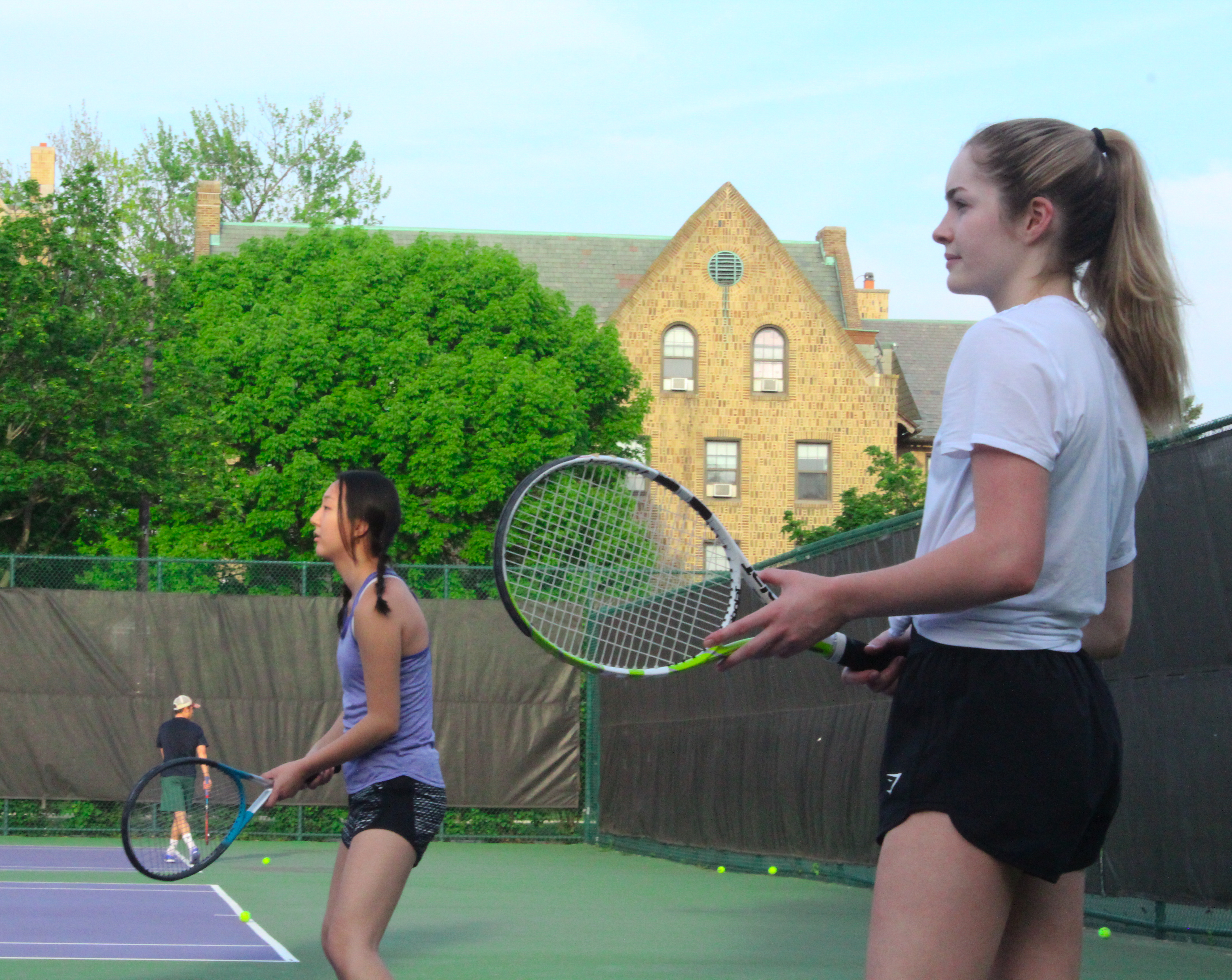 Two students playing tennis on an outdoor court